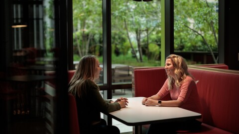 Two women engage in a conversation in an Amazon headquarters building.