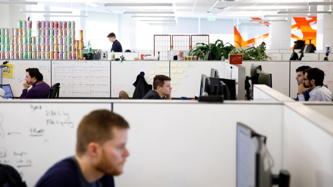 People working in cubicles in Amazon's Pittsburgh, PA office. There is an orange accent color.