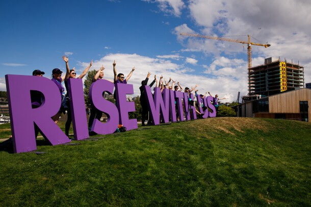 """""""Rise with us"""" sign for the Special Olympics USA Games, set on a hillside in Seattle. The purple letters are shown with more than a dozen Amazon employee volunteers waving and smiling, as they welcome athletes to the closing ceremony."""