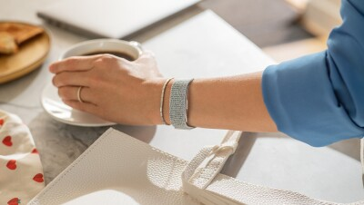 A woman wears a Halo band on her right wrist. She is reaching for a cup of coffee on a tabletop.
