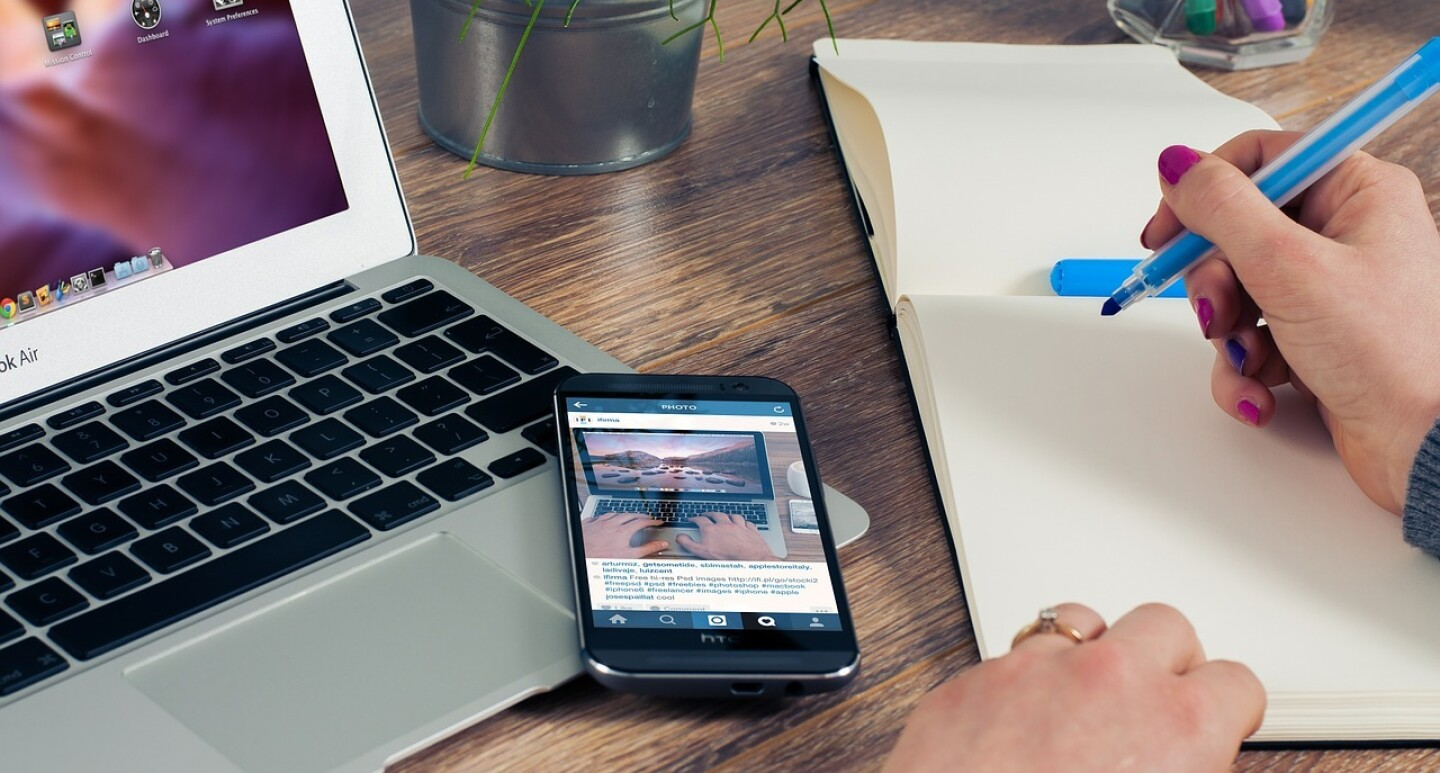 Picture of a laptop and a notepad with a lady's hand holding a pen against a notepad