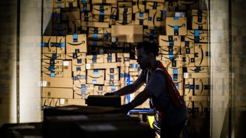 An Amazon associate, dramatically back lit by his work light, stacks shipping boxes labeled with the Amazon smile to the ceiling of a semi trailer.