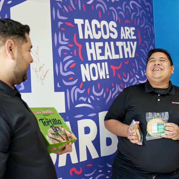 Ronald and Anthony hold their products in front of a Mr. Tortilla promotional sign.