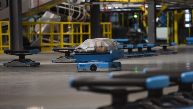 An image of small, blue robots with packages on them rolling through an Amazon sortation center.