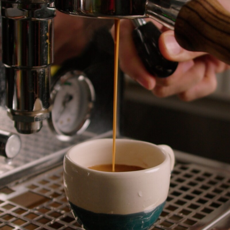 Freshly brewed coffee flowing into a ceramic cup