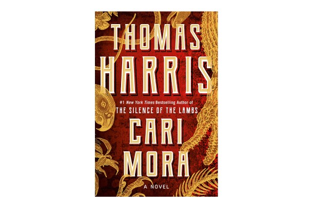 "Book cover for the novel ""Cari Mora"" shows tall, ivory letters with the author's name, and the book title. The background is a deep red, with golden plant leaves swirling about."