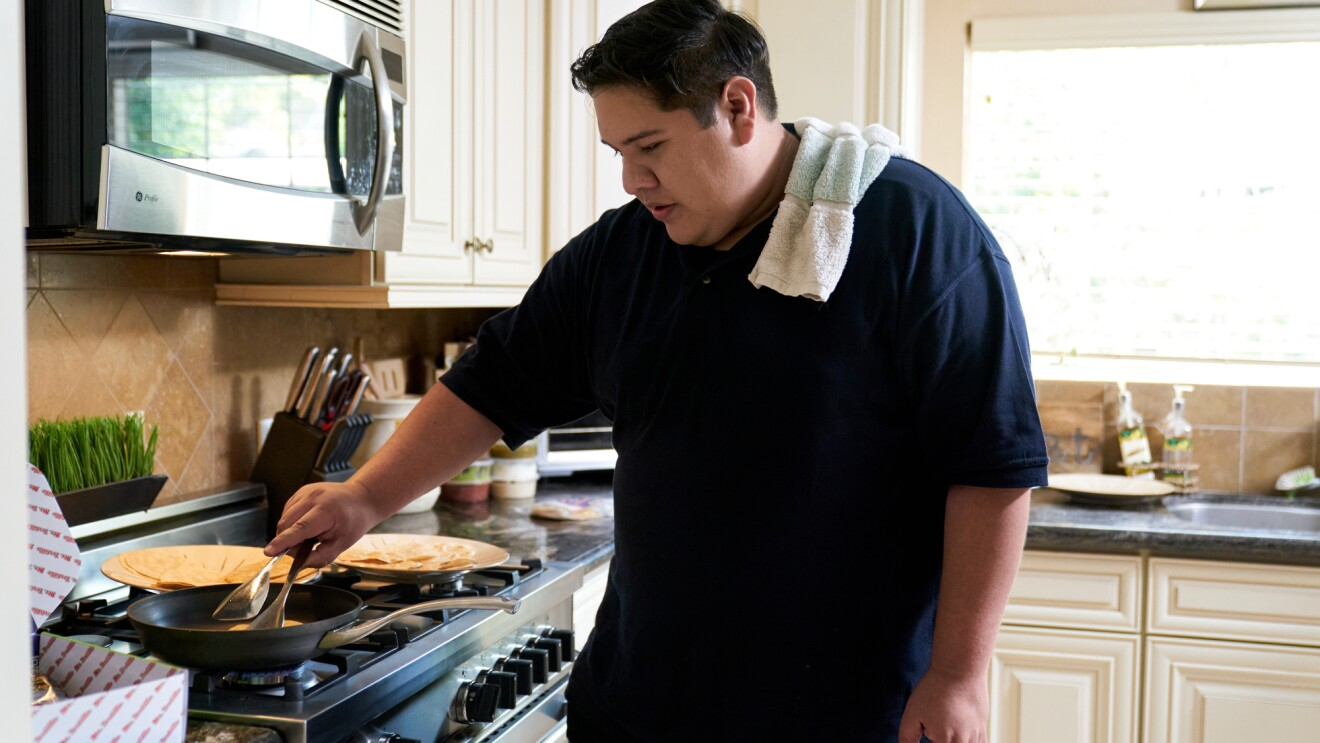 A man makes tortillas in a home kitchen.