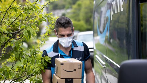 A delivery driver wearing a face mask walks alongside an Amazon Prime delivery van, carrying packages.