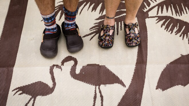 A man and woman photographed from the shins down. Both wear clogs. The man wears cozy socks. The woman goes sockless. They stand on an outdoor mat with images of flamingoes and a palm tree.