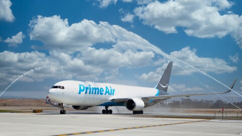 An Amazon Air plane on a tarmac with celebratory fireworks going off around it.