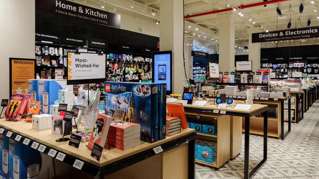 "The view inside Amazon 4-star store. Tables are stacked with books, toys, devices, kitchen implements, and cookbooks.  ""Home & Kitchen,"" ""Devices & Electronics,"" and Toys, Kids & Baby section signage is visible."