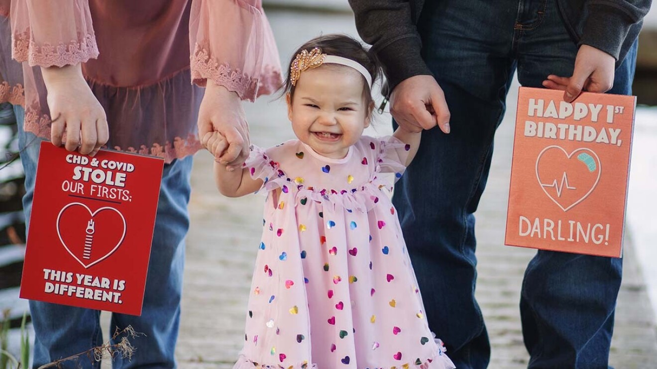 A toddler stands holding her mom and dad's hands. Her parents hold large greeting cards on either side of her.
