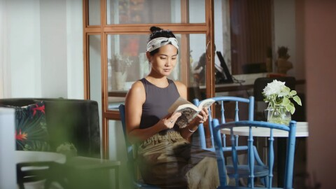 Dione Song, CEO of Love Bonito, reading a book at a cafe
