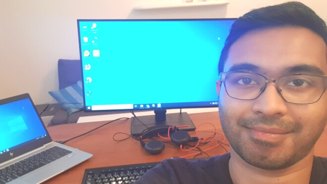 Selfie photo of a man sitting in front of a desk with a computer on it.