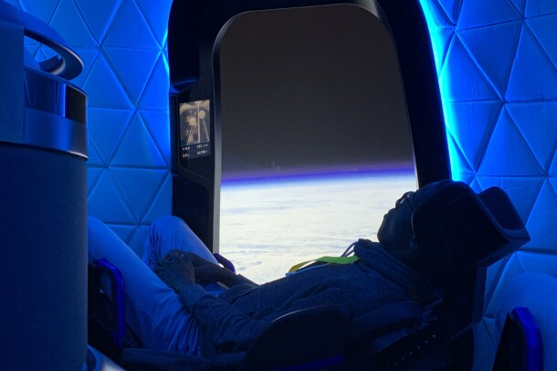 A teen lounges in a seat within the Blue Origin capsule.