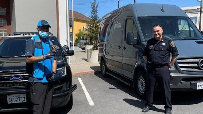 A police officer and a delivery driver stand near a delivery van.