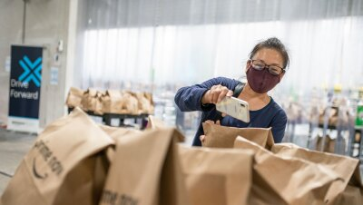 A woman wearing a mask and glasses uses her smartphone to scan Prime Now delivery bags.