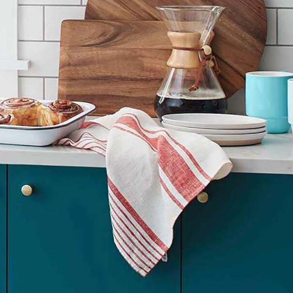 Image from within a kitchen, with cinnamon rolls, a Chemex coffee maker, towel, cutting board, mugs, and plates on the counter.