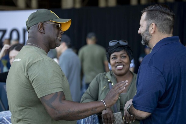Three people engage in a conversation at the celebration honoring military associates at Amazon.