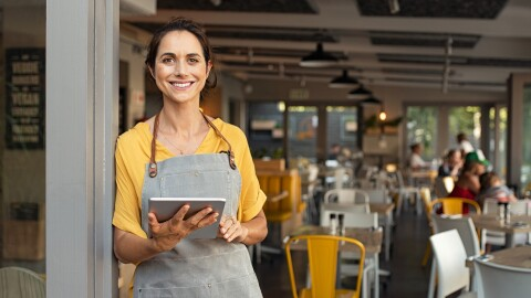 A woman holding a tablet and wearing an apron leans against a post and smiles at the camera. Behind her people are seated at tables in a cafe or restaurant.