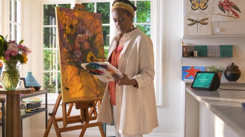 A mature woman works on a painting in her home. Behind her, an Alexa device is on the kitchen counter.