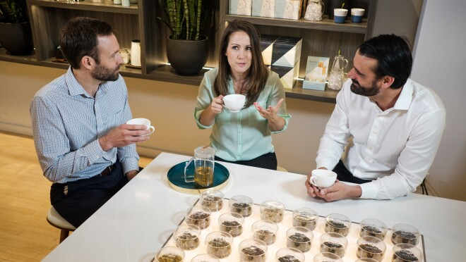 Two men and a woman sit at a counter, holding teacups. In the foreground are rows of round containers of loose leaf tea.