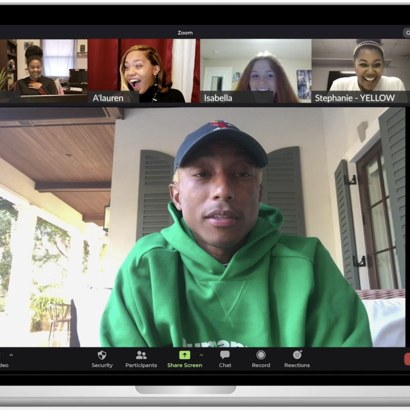 A laptop computer screen shows Pharrell speaking with four women