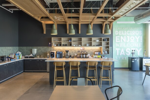 The kitchen area of an Amazon office building in San Diego. Open ceilings and industrial lighting are over an island. In the background are coffee makers, water machines and other kitchen accessories.
