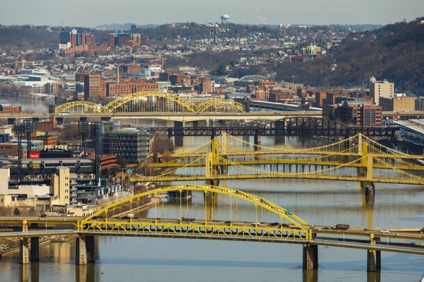 Four yellow bridges across a river span both banks in Pittsburgh, PA. There is light snow on the ground and the sky is clear.