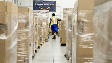 A man wearing shorts, tennis shoes, a t-shirt and safety vest walks between pallets of supplies in Amazon's Disaster Relief Hub