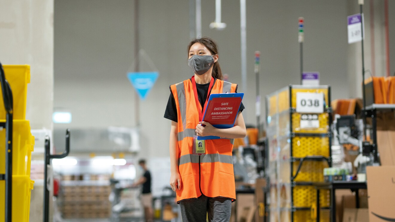 An associate is walking on the floor at Amazon's Fulfillment Center in Singapore with a safety mask on and a file in her hand