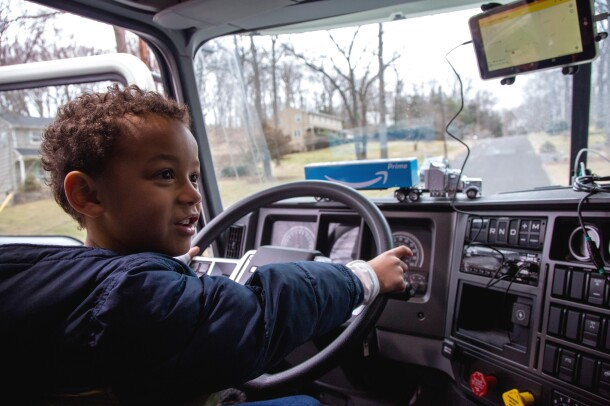 A young boy sits in the cab of a semi truck and puts his hands on the steering wheel. His toy truck is with him just in front of the steering wheel.