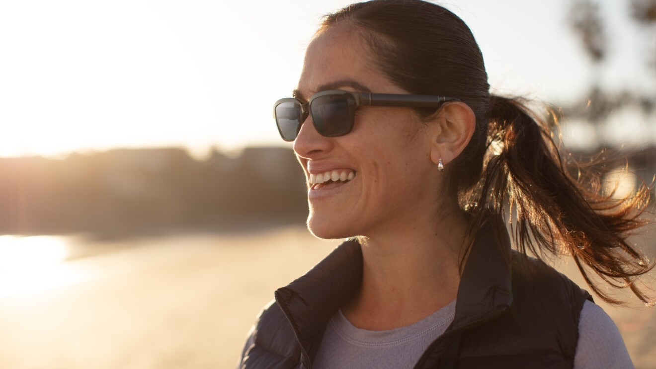 A woman wearing Echo Frames sunglasses while smiling watching the sunrise.