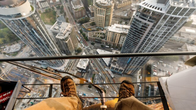 A man in a khaki pants and lace up shoes stands atop a crane, high above Seattle, WA.