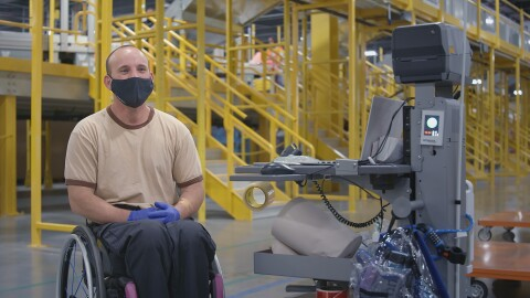 An Amazon Fulfillment Center employee wearing a black mask and protective blue gloves sits in a wheelchair next to a mobile computer desk.