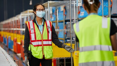 An image of two women working in an Amazon fulfillment centre. They are both wearing safety vests and masks and smiling at each other.