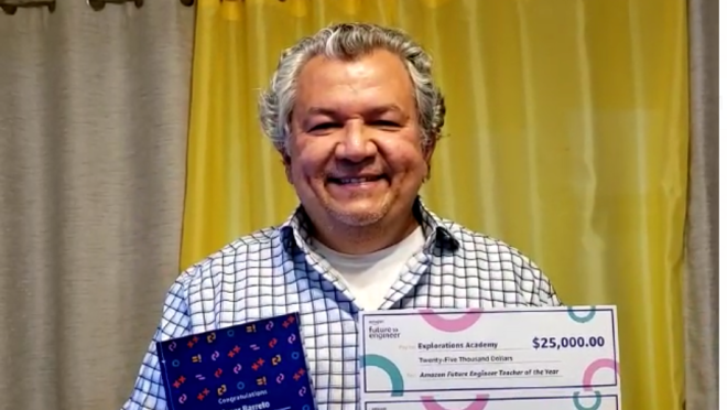 A man smiles for a photo holding a paper that says he won the Amazon Future Engineer Teacher of the Year award and two checks--one for $25,000 and the other for $5,000.
