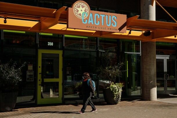 """A pedestrian wearing a medical mask passes a restaurant with """"CACTUS"""" on its sign."""