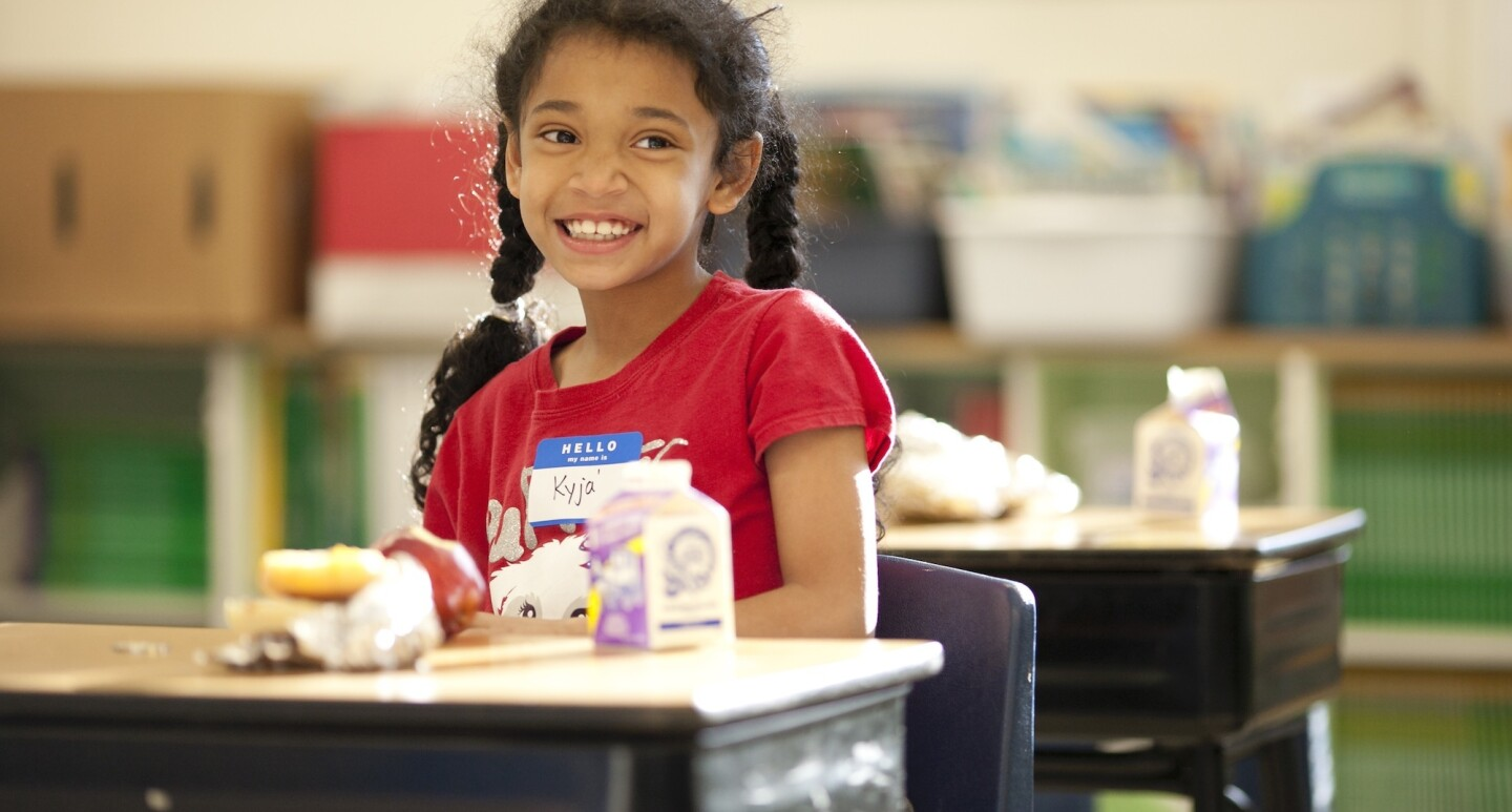 A smiling student enjoys a lunch at her school desk.