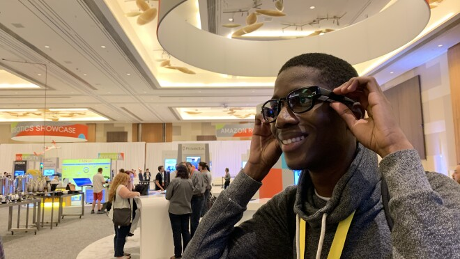 A teen smiles, as he tries on North smart glasses, inside a conference hall.