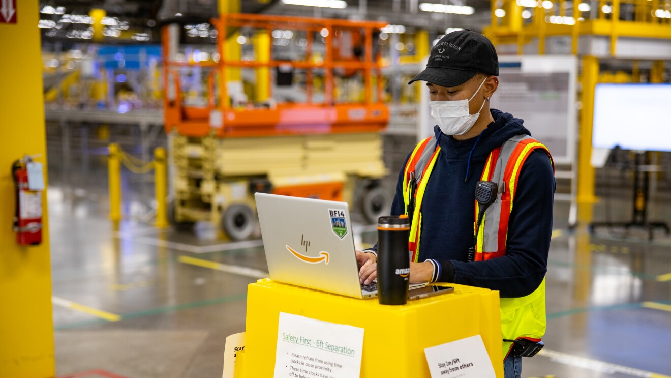 A man stands near a stack of yellow totes, typing on his computer in an amazon fulfillment center.