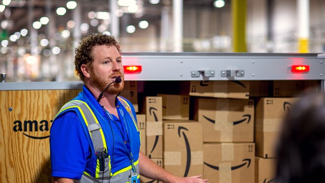 A man wearing a safety vest and a microphone headset stands in front of a display of boxes with the Amazon smile logo.