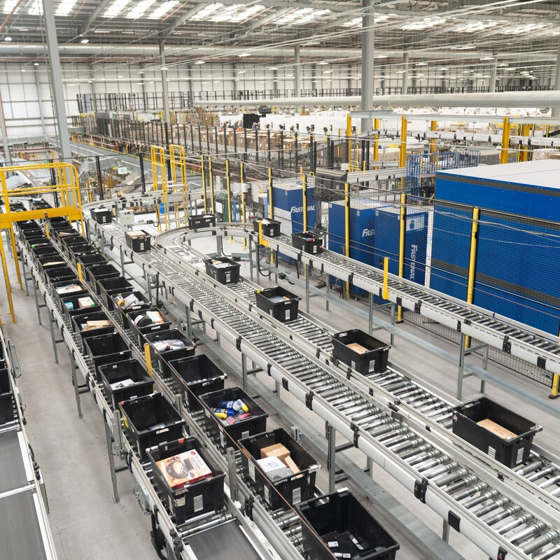 The view inside an Amazon fulfillment center. Boxes of product are show on conveyor belts.