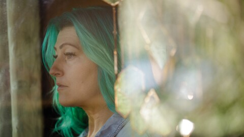 A woman with long green hair photographed in profile.