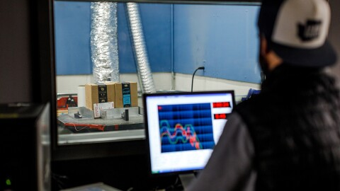 Aman sits behind a computer in a packaging lab and watches while tests are executed
