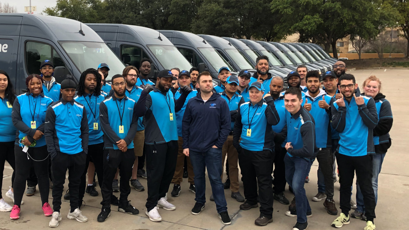 Employees at Patriot DSP stand as a group in front of a fleet of Prime delivery vans.