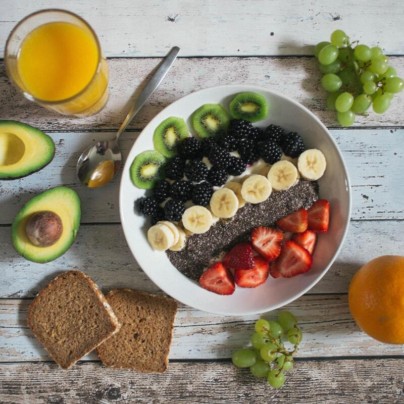 Image of a breakfast table which has fresh fruits, bread and cereals