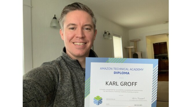 Karl Groff  holds up his ATA diploma and smiles for a picture.