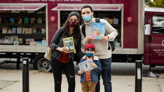 """An image of a man and a woman standing with a child in front of a truck with books inside of it that reads """"Bringing Books to Readers."""" All three people in the photo are holding up a book as they stand for the photo wearing face masks."""