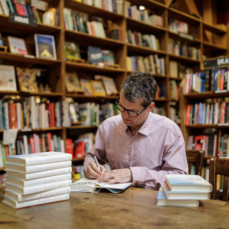 An author sits at a table and signs his book in a bookstore, surrounded by shelves of other book titles.